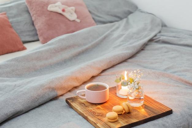 Té de hierbas con macarrones y velas en bandeja de madera en la cama