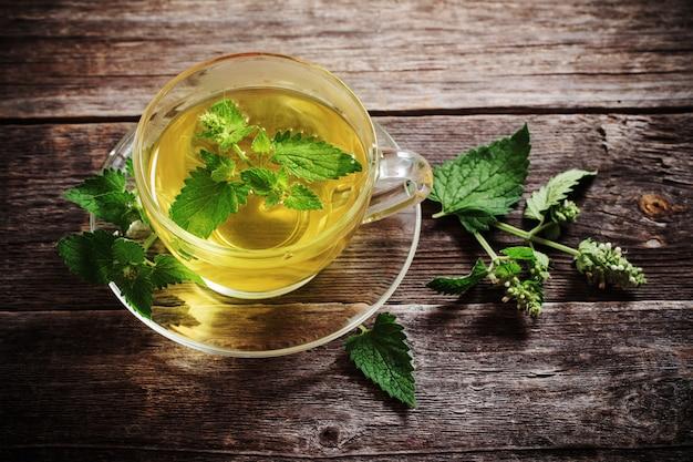 Té de hierbas melissa verde en vaso de vidrio sobre mesa de madera