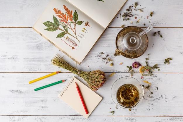 Té de hierbas en mesa de cuchara de madera con libro y lápices de colores