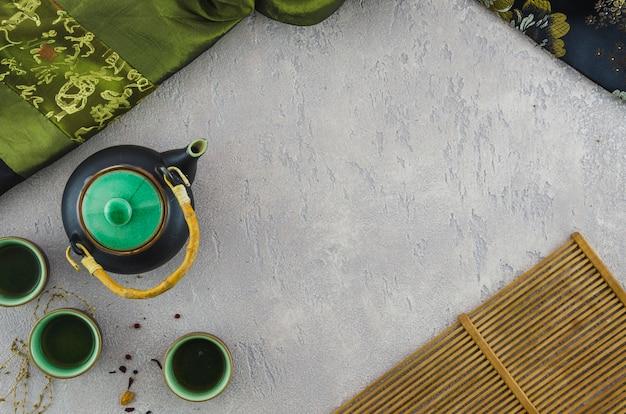 Té de hierbas oriental con textiles asiáticos y mantel sobre fondo texturizado