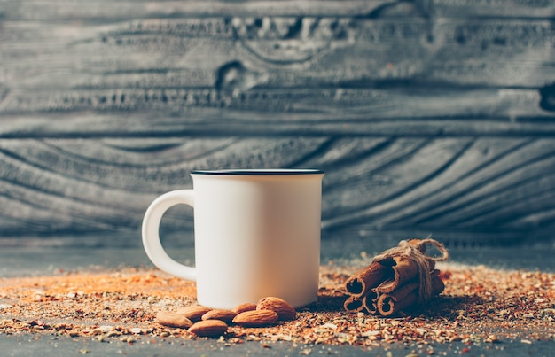 Té y hierbas secas con canela seca y almendras en mesa de madera, vista lateral,