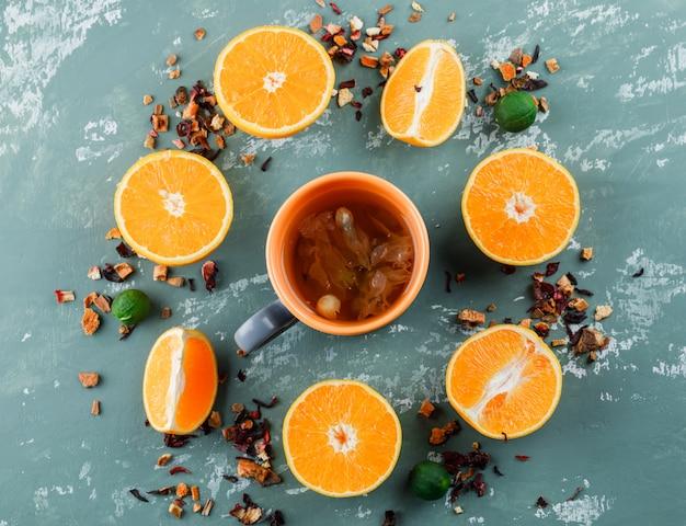 Té con hierbas secas mixtas, naranjas, limas en una taza sobre la superficie de yeso