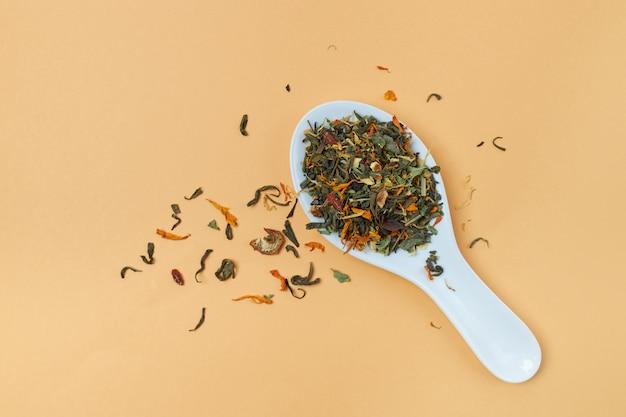 Té de hierbas seco a base de pétalos de plantas medicinales en cuchara sobre naranja