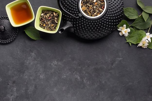 Té de hierbas y su ingrediente dispuestos en fila en la parte superior del fondo negro