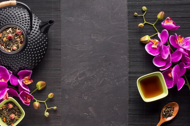 Té de hierbas con su ingrediente seco y flor de orquídea en mantel negro