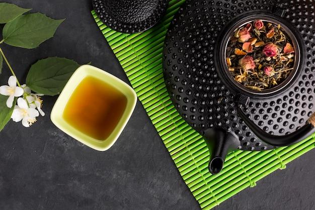 Té de hierbas con su ingrediente seco en mantel verde