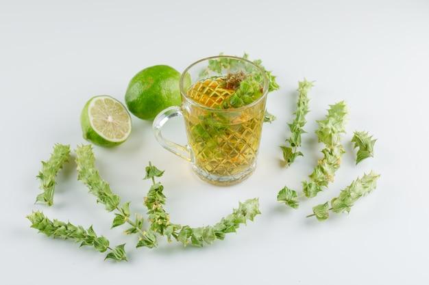 Té de hierbas en una taza de vidrio con hojas, lima vista de ángulo alto sobre un blanco