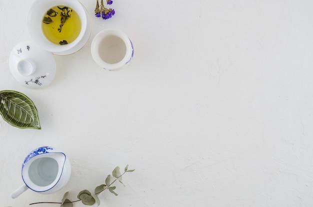 Té de hierbas en un tazón de cerámica china; jarra y una taza aislada sobre fondo blanco