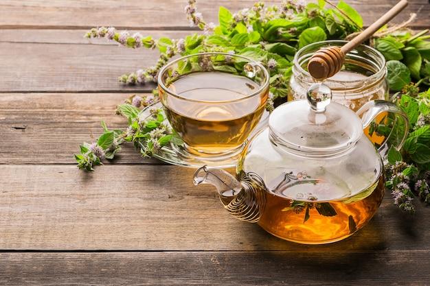Té con hojas frescas de menta bálsamo de limón en una taza y tetera sobre madera