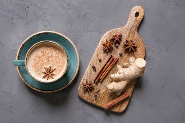 Té indio masala en taza con especias en mesa de hormigón gris. vista superior.