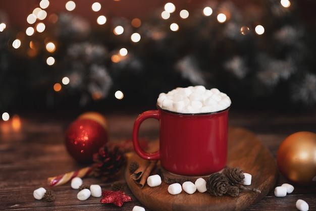 Té de invierno caliente en una taza roja con galletas navideñas en forma de estrella y bufanda caliente