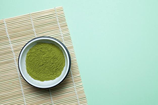 Té japonés o chino matcha en polvo en un tazón de té sobre una estera de bambú