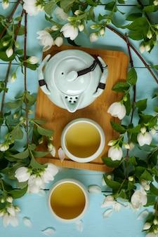 Té de jazmín. té orgánico de flores naturales. té de jazmín en tazas verdes, tetera y ramas de jazmín.