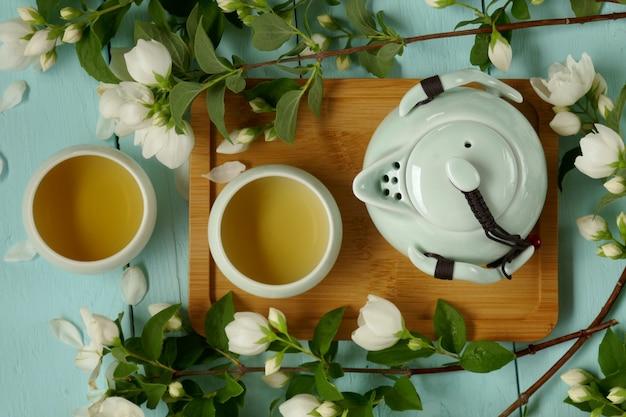 Té de jazmín. té orgánico puro de flores. té de jazmín en tazas redondas de color verde claro, tetera y ramas de jazmín.