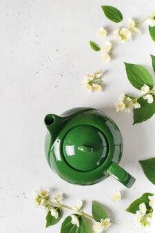 Té de jazmín con tetera, flores y hojas sobre fondo blanco, copie el espacio, vista superior, vertical