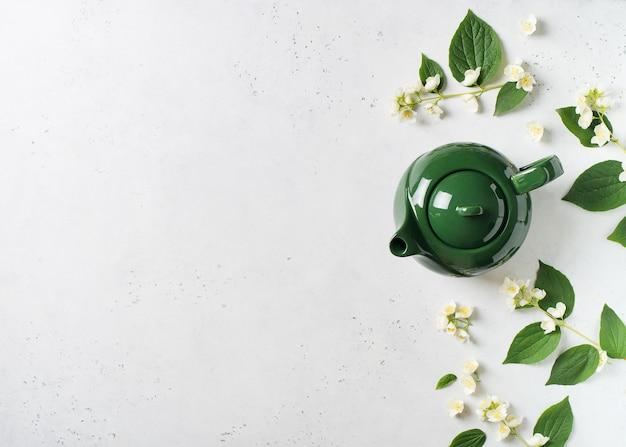Té de jazmín con tetera, flores y hojas sobre fondo blanco, espacio de copia, vista superior