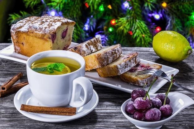 Té de jengibre y pastel de cereza cerca del árbol de navidad