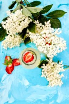 Té de kombucha con flor de saúco y fresa sobre fondo azul. .
