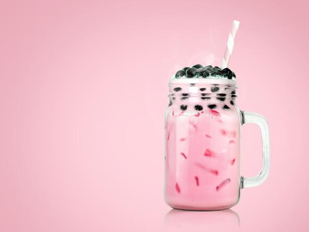 Té con leche dulce con burbujas en vidrio transparente y pajitas en rosa