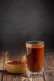 Té con leche tailandés y cacao en botella sobre mesa de madera