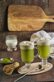 Té con leche verde matcha, polvo de matcha y batidor de bambú sobre fondo de madera, vertical.