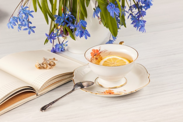Té con limón y bouquet de prímulas azules sobre la mesa