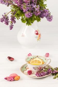 Té con limón y bouquet de prímulas lilas sobre la mesa