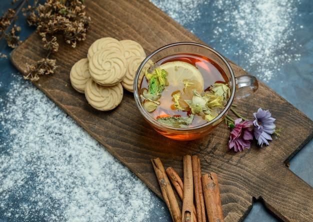 Té de limón con galletas, hierbas secas, palitos de canela en azul sucio y tabla de cortar, plano.