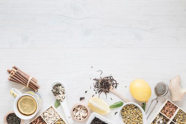 Te de limón; hierbas; colador y jengibre arreglan en mesa de madera