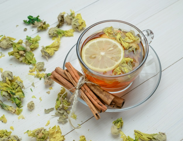 Té de limón con hierbas secas, palitos de canela en una taza sobre la superficie de madera, vista de ángulo alto.