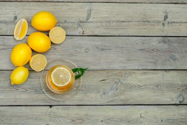 Té de limón con limón y lima en mesa de madera