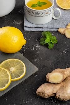 Té de limón siciliano con jengibre y hojas de menta sobre piedra de pizarra.