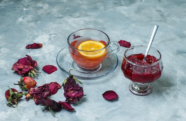 Té de limón en una taza con rosas secas, mermelada, cuchara vista de ángulo alto sobre una superficie azul grunge