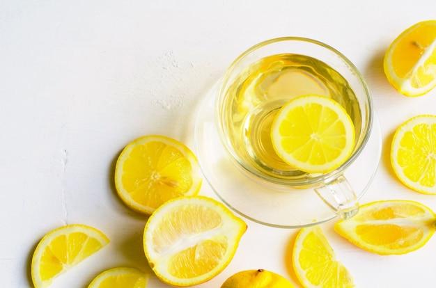 Té de limón en una taza transparente sobre blanco con rodajas de limón