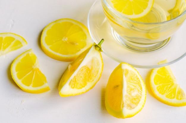 Té de limón en una taza transparente sobre fondo blanco con rodajas de limón