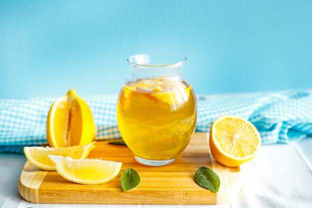 Té de limón verde con mantel y fruta de limón.
