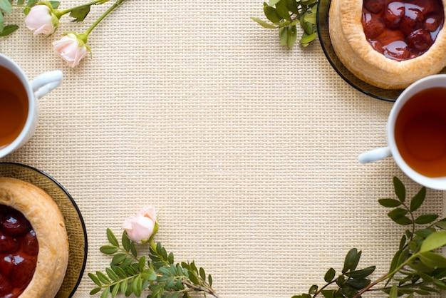 Té de la mañana con productos horneados, flores color de rosa en la mesa. pastel con fresas. en una servilleta vieja