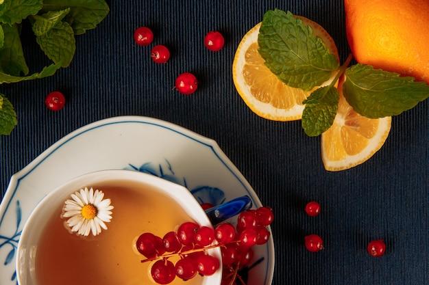 Té de manzanilla en taza y salsa con limón, bayas de grosella roja dispersas y hojas verdes sobre fondo mantel azul oscuro. vertical. vista de ángulo alto
