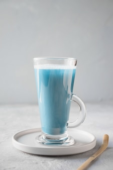 Té matcha azul en vidrio con leche en la mesa gris