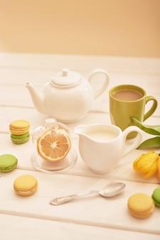 Té con menta y limón en la mesa con macarrones y tulipanes amarillos