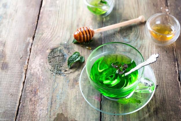 Té de menta marroquí con hojas de menta fresca y miel sobre fondo de madera vieja