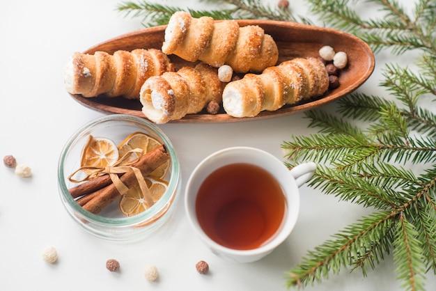 Té navideño con pasteles, una rama de abeto verde, galletas dispersas, una galleta de caracol con crema de proteínas