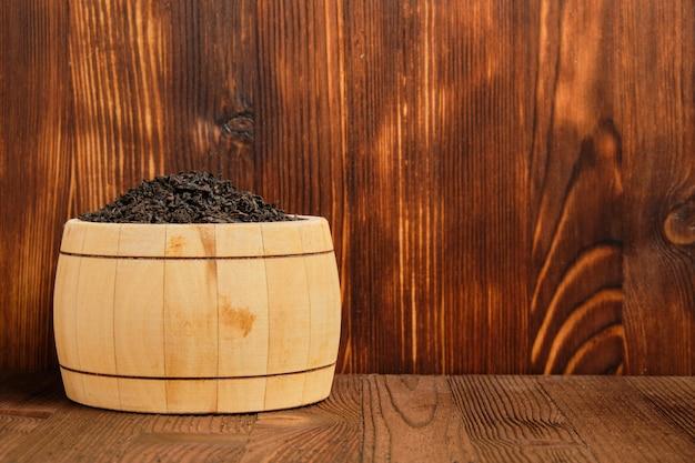 Té negro en un barril contra el fondo de un fondo de madera quemada. copia espacio