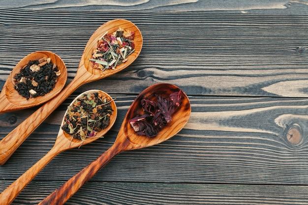 Té negro con hierbas en cucharas de madera sobre una plancha de madera