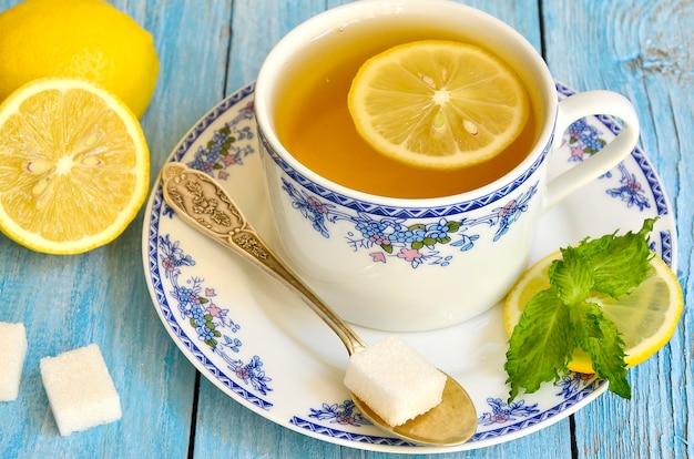Té negro con limón y menta en la mesa de madera azul