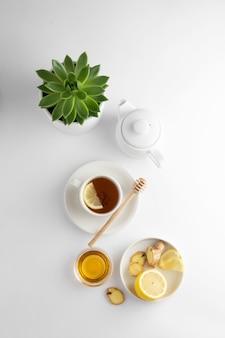Té negro con limón y miel sobre un fondo blanco. taza de té caliente aislado, vista superior plana. endecha plana. bebida de otoño, otoño o invierno. copyspace