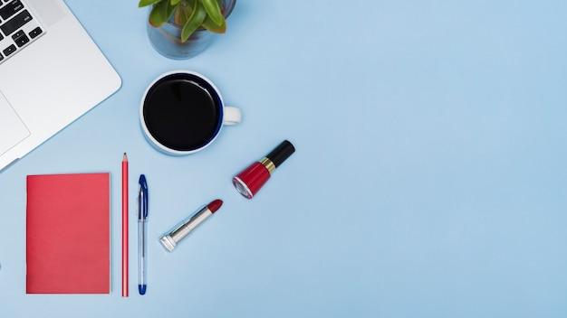 Te negro ordenador portátil; planta; papelería y lápices labiales sobre fondo azul