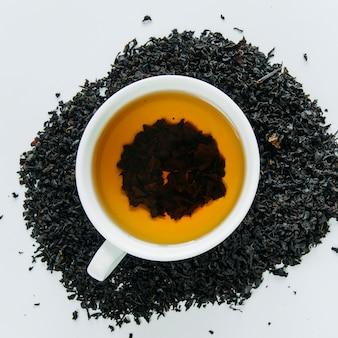 Té negro en una taza y hojas secas sobre fondo blanco.