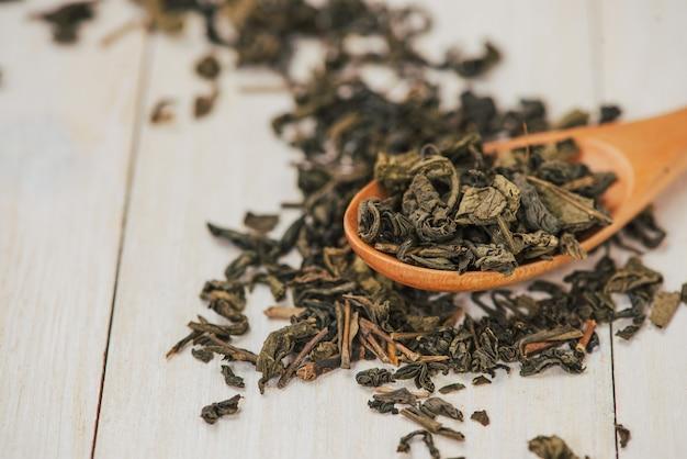 Té negro en una taza de vidrio y hojas de té en una cuchara de madera sobre fondo de piedra negra.