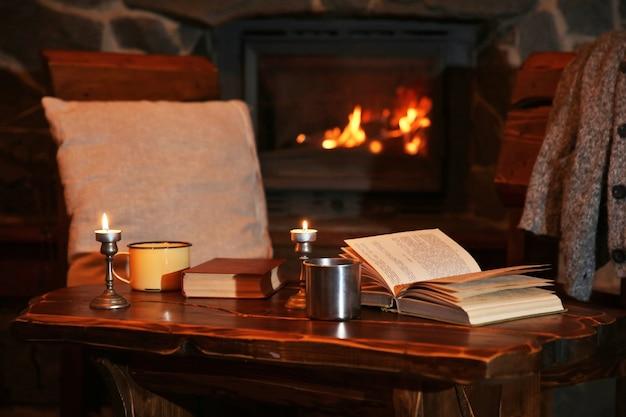 Té o café caliente en taza, libro y velas en la mesa de madera vintage. chimenea como fondo